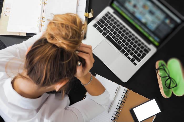 femme tient sa tete pour problemes liés aux dettes