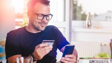 homme avec carte de credit dans la main et telephone pour appeler pour réduire ses dettes