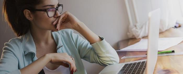 femme reflechissant devant son ordinateur